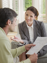 Businesswoman discussing paperwork with man