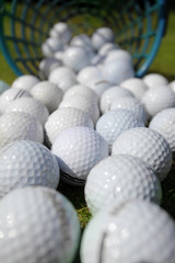 Golf balls pouring out of basket onto grass