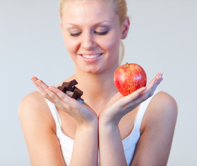 Young woman showing chocolate and apple