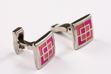 a pair of pink cuff links