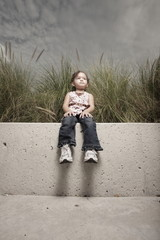 Young girl sitting on a ledge