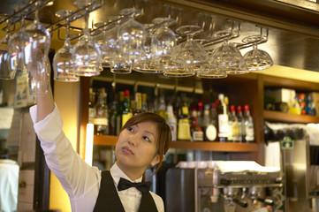棚からグラスを取るウェイトレス