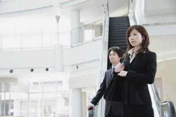 エスカレーターの前に立つ女性と男性