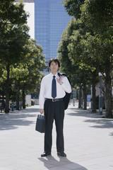 スーツの上着を肩に掛けて立つ男性