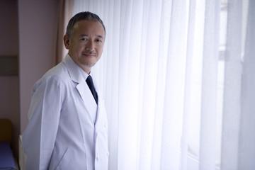 窓際に立つ男性医師