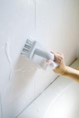 浴室を洗う女性