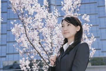桜の花の前に立つスーツ姿の女性