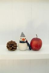 雪だるま人形と松ぼっくりとりんご
