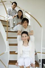 階段に座る中年夫婦と息子と娘