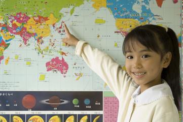 世界地図を指差す小学生