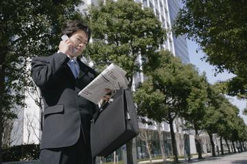 携帯電話で話しながら新聞を読む男性