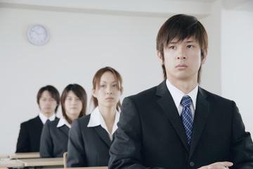 会議室に着席するスーツ姿の若い男女4人