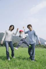 草原で娘を持ち上げる両親