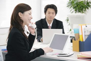 pc画面を眺めながら電話で会話する女性