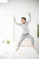 ベッドでジャンプする男の子