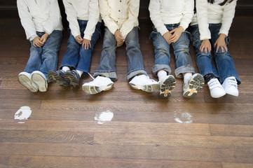 廊下に並んで座る小学生の足