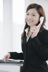 机に腰掛けて電話をする女性