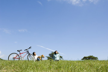 自転車を止めて犬と遊ぶカップル