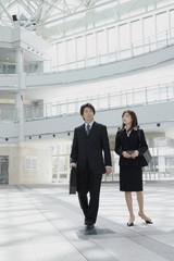 オフィスビルのロビーに立つ男性と女性