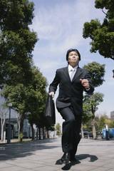 スーツ姿で走る男性