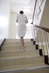 階段を上がる女性看護師