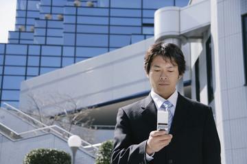携帯電話の画面を眺める男性