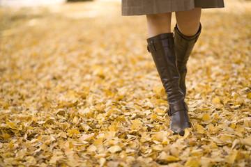 落ち葉の上を歩く若い女性の足