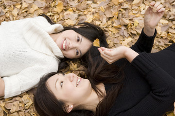 落ち葉の上で仰向けに寝る2人の女性