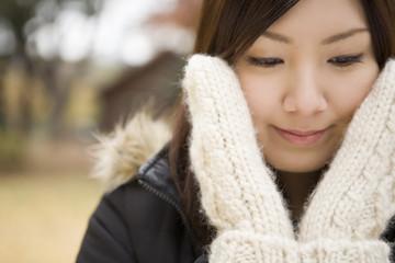 手袋を着け頬を触る若い女性