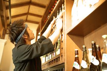 棚のボトルを探す男性店員