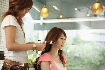 髪をアイロンでセットする美容師と女性