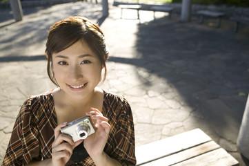 デジタルカメラを持つ若い女性