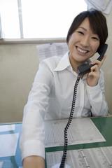 電話応対する若い女性