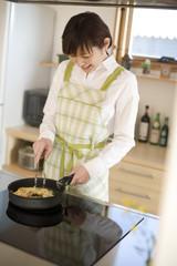 スパゲッティを調理する女性