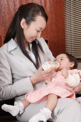 子供にミルクを与える母親