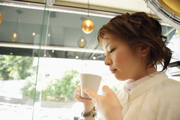 美容室でコーヒーを飲む女性