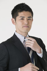 ネクタイを整える若いビジネスマン