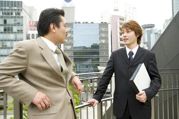 屋外で談笑する男性2人