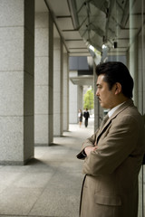 オフィスビルの前で腕組みをする男性
