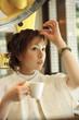 美容室で自分の髪をチェックする女性