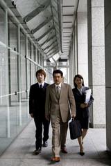 オフィスビルの側を歩く男女3人