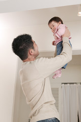 赤ちゃんを持ち上げる父親