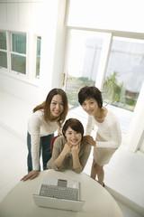 パソコンを囲む若い女性たち