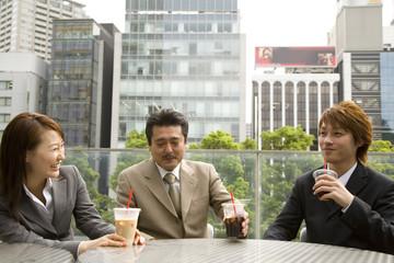 屋外で談笑する男女3人