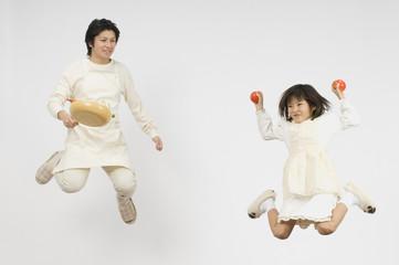 トマトを握る娘とフライパンを持つ父親
