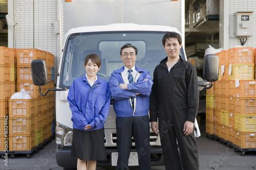 トラックの前に立つ社員