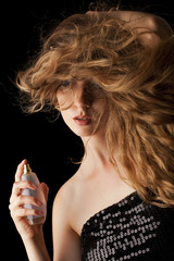 woman with flipping hair applying perfume on her body