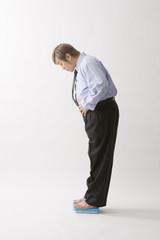 体重計に乗る中年男性