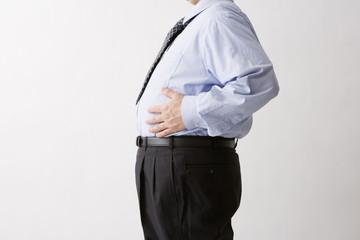 腹部に手を置く中年男性