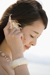 貝殻に耳をあてる女性